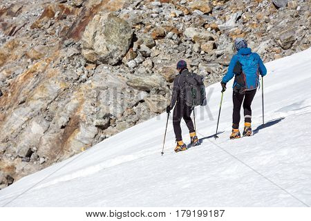 Mountain Climbers Man and Woman walking on steep Ice Slope using high Altitude Boots Crampons and other alpine Gear