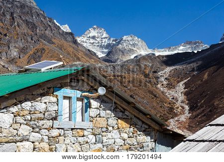 Mix of Modern Technologies and traditional rural Architecture in Nepal Mountains solar Cell and Internet Hot Spot on the wooden Roof of traditional handcrafted Stone Hut.