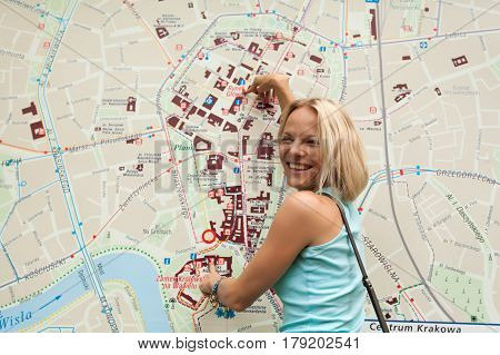 A young pretty blond woman in a blue T-shirt is standing on the background of a large map of Krakow and points at it. The central part of the city. Poland. Tourism.