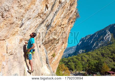 Mature male Climber arranging Belay on orange Rock above Forest and Village vertical composition