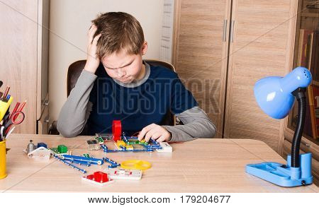 Puzzled teen boy doing school electronic project in his room at home.