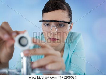 Digital composite of Close up of woman with electronics against blurry blue background