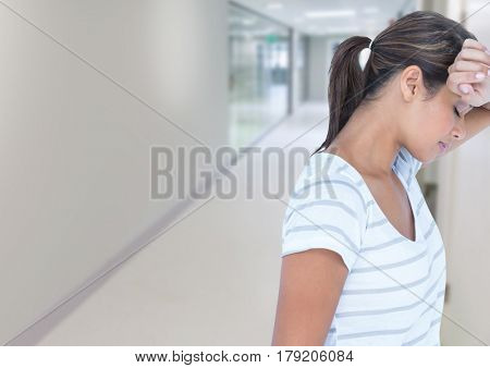 Digital composite of Tired woman leaning on wall in corridor