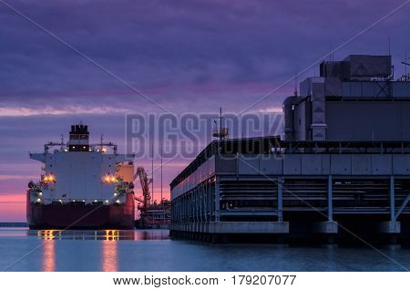 LNG TERMINAL AT DAWN - Tanker moored to the quay of the gas terminal