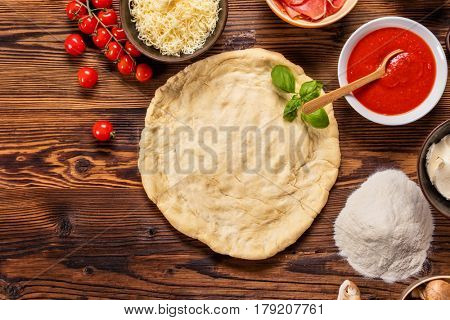 Pizza dough with ingredients served on wood, shot from above. Lots of raw food pieces ready for pizza cooking