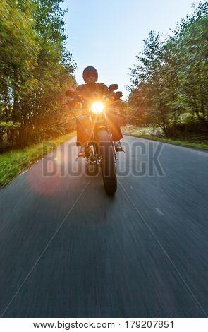 Dark motorbiker riding high power motorbike in nature with beautiful sunrise light