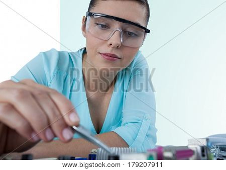 Digital composite of Woman with electronics against green and white background
