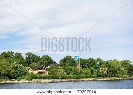 Stockholm, Sweden - June 6, 2016: Coastal Houses With Swedish Flags And Cycling People, On An Island