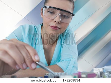 Digital composite of Woman with electronics against white background with stripes