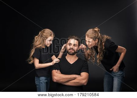 Mother And Daughter Quarreling At Father Sitting With Crossed Arms On Black