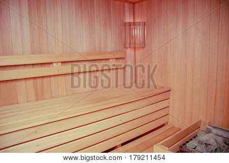 Interior of a wooden sauna room with lamp in the corner