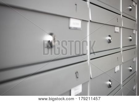 Rows of aluminum mail boxes for concepts such as safety and security business communication and concepts. Shallow depth of field.