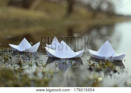 Origami paper ship sailing in river. Paper boats made from mathematics notebook paper.