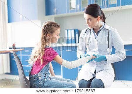 Woman Doctor Bandaging Hand Of Little Girl In Hospital