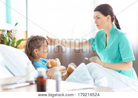 Side View Of Nurse Checking Temperature Of Sick Little Girl In Hospital Bed