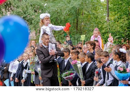 Tyumen, Russia - September 1, 2012: School 43. Older boy, teenager, caucasian, carries small schoolgirl with the bell. First ring in new school year