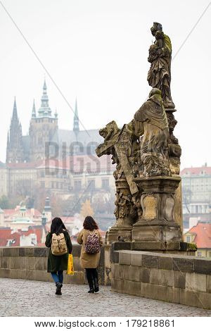 Sculpture on Charles Bridge with view at Hradcany Castle.