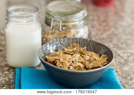 Portion of crunchy muesli flakes with oats in a small bowl with milk on blue napkin