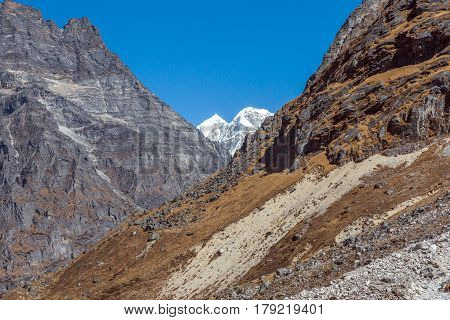 Layered Mountain Terrain with Rocks Moraine Grassy Slope and snowcapped Summit
