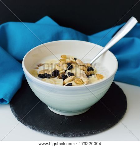 Square photo of oatmeal porridge cooked with milk nuts banana raisin and served with a metal spoon on black slate board with blue napkin. Blue bowl with milky porridge. Healthy breakfast