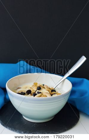 Porridge with oats milk banana slices raisin and nuts served in a blue bowl with spoon on black slate board with blue napkin. Vertical photo. Healthy eating concept. Breakfast meal