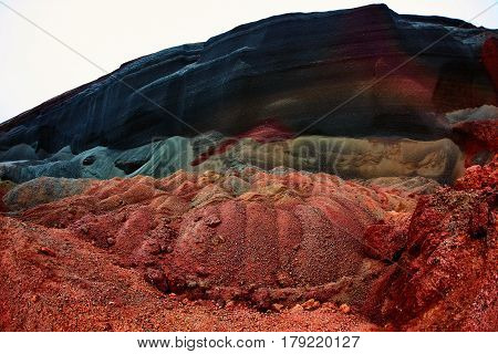 Quarry in a volcano crater in Iceland. Stone rock red and black. Tourist takes picture
