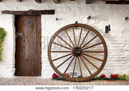 wooden cartwheel and rustic door in typical andalusian patio. Cordoba Spain