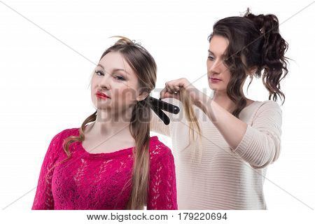 Working serious hairstylist and woman on white background