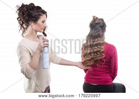 Woman from back and hairstylist with hairspray on white background