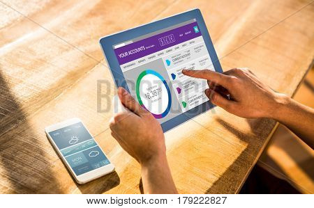 Graphic image of bank account web site against over shoulder view of casual man using tablet