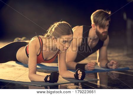 Young Sporty Man And Woman Doing Plank Exercise On Mats And Looking Away