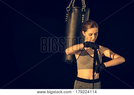Sportswoman Wraping Hands With Tape With Punching Bag Behind On Black