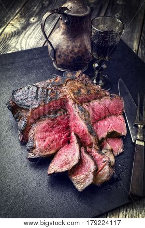 Barbecue dry aged Wagyu Bistecca alla Fiorentina as close-up on a black slate