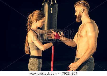Sportswoman Wraping Man's Hand With Tape With Punching Bag Behind