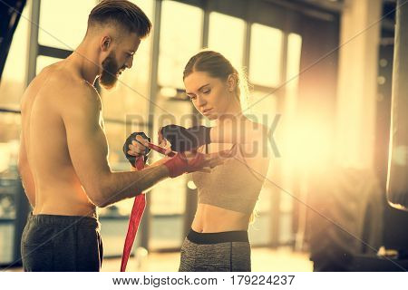 Sportswoman Wraping Man's Hand With Red Tape In Sports Center