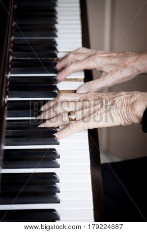 close up of an older womans hands playing the piano.