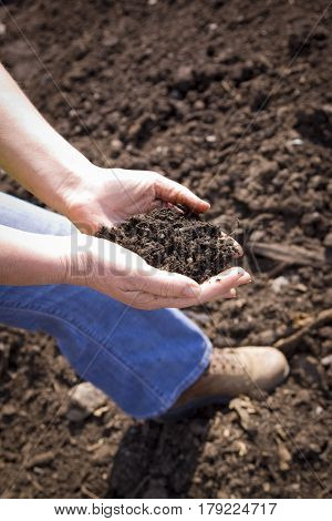 A woman holds up a handful of soil from a compost area.