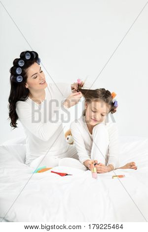 Mother Curling Hair To Daughter Applying Nail Polish On Toenails