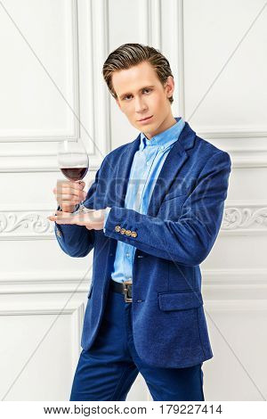 Good looking young man with a glass of red wine standing in luxurious apartments. Men's beauty, fashion model. Sommelier.