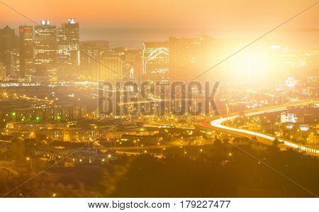 Blurry animated flare against high angle view of illuminated cityscape