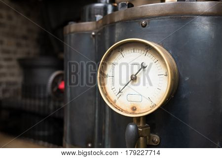 Close up view of an old industrial pressure gauge.