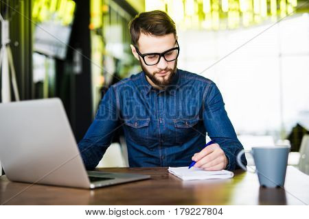 Man Taking Notes Down From His New Laptop Computer At Work In The Morning Office