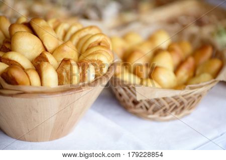 Bowl of oven fresh baked patties russian pirozhki on table
