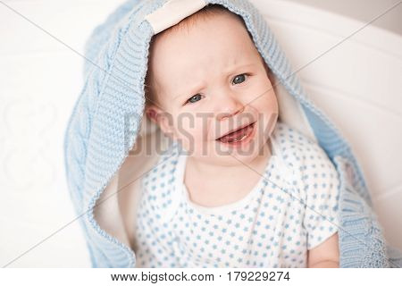 Crying baby 3-6 month old sitting under knitted blanket in bed. Sleeping bedtime. Childhood.