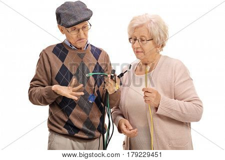 Confused seniors looking at different types of electronic cables isolated on white background