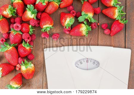 weighting scale against fresh strawberries and raspberries on wooden board