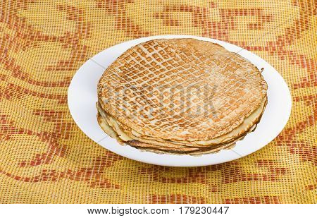 Russian pancakes on a white plate .