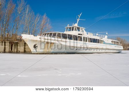 An old pleasure boat iced-bound on a winter berthing.