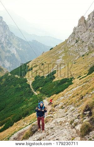 Two young men in hiking gear wearing backpacks walking together along a rocky trail on a rugged mountain range