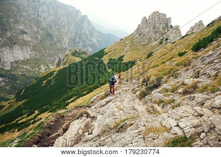 Two young men in hiking gear wearing backpacks walking together along a rugged trail high up in the mountains